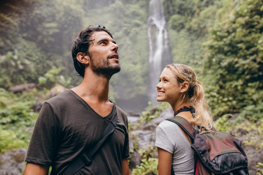 Young couple with backpack hiking in nature.